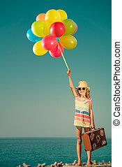 Happy child with colorful balloons on summer vacation