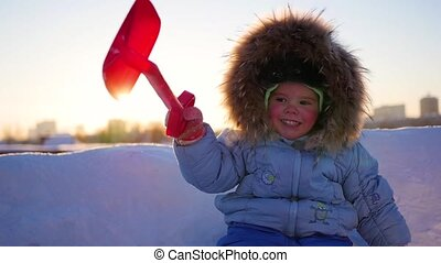 happy child with fun laughing in winter park on a sunny day. snow winter landscape. outdoors