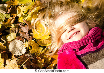 happy child with long blond hair in autumn time