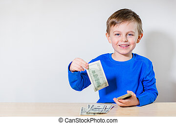 Happy child with money dollar, little businessman. Pile of United States dollar hundred USD banknotes