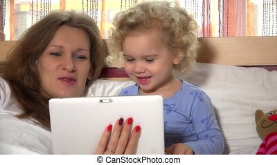 Happy child with mother babysitter having fun with tablet computer in bed.