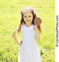 Happy child with sweet lollipop outdoors in summer day