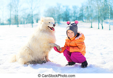 Happy child with white Samoyed dog on snow in winter park