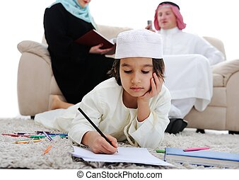 Happy child working on homework at home with his family