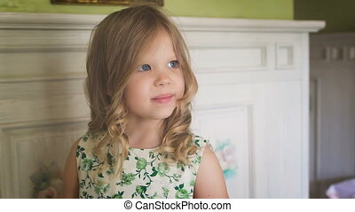 Happy childhood. A cute little girl is smiling. A pretty little blondie is A cute little girl is stretching in the morning.