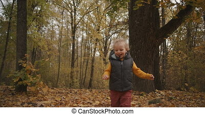 happy childhood and fun time at nature, little child boy is running in forest at autumn day, stepping over dry foliage on ground, cute smiling face of toddler