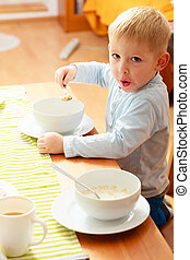 Happy childhood. Blond boy kid child eating corn flakes cereal with milk breakfast morning meal at the table. Home.