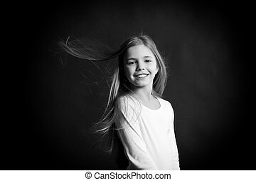 Happy childhood concept. Child model smiling with blowing long hair. Girl with adorable smile on dark background. Fashion, look, hairstyle. Happy childhood concept.