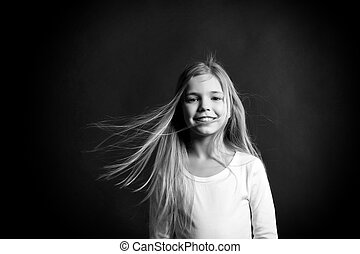 Happy childhood concept. Girl with adorable smile on dark background. Beauty and hairdressing salon. Fashion, look, hairstyle. Child model smiling with blowing long hair