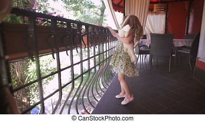 Happy childhood. Happy blonde girl in the dress having fun dancing at a bright balcony. A sweet blondie is dancing in the beautiful dress.