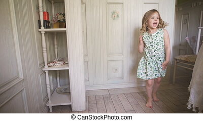Happy childhood. Happy blonde girl in the dress having fun dancing indoors in a sunny white room at home or kindergarten. A sweet blondie is dancing in the beautiful dress.