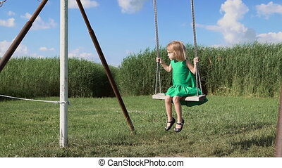 Happy childhood. Summer. A charming little blonde girl is swinging at a green field. A cute blondie having fun swinging.