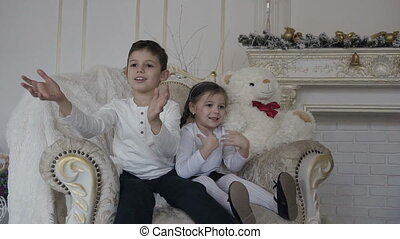 Happy children - a boy and a girl are sitting on a large chair and catch gifts in golden boxes. Christmas evening