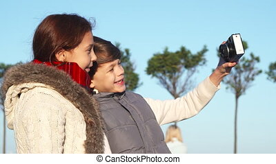 Happy children are doing selfie on camera