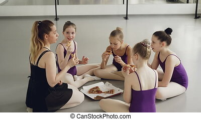 Happy children ballet students and their teacher are eating pizza during lunch break between dancing lessons. Girls are talking, smiling and enjoying delicious food.