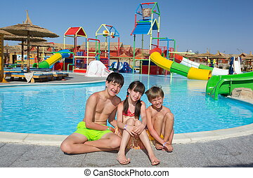 Happy young brothers with sister by swimming pool; colorful, water slides or chutes in background.