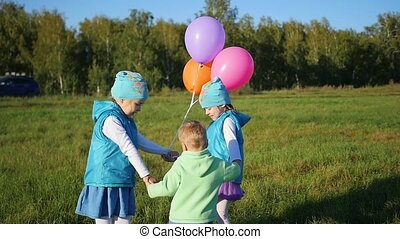 Happy children circling holding hands in the Park with balloons. Children's holiday in the open air