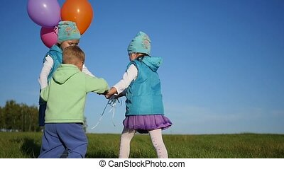 Happy children circling holding hands in the Park with balloons