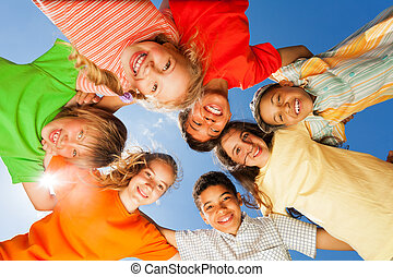 Happy children close in circle on sky background
