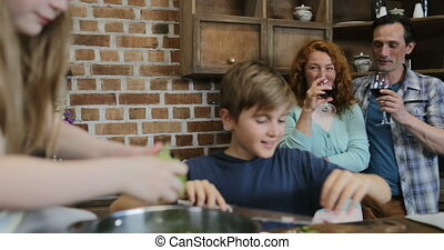 Happy Children Cooking Salad Talking With Parents Drinking Wine, Cheerful Family Preparing Food Together In Kitchen