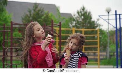 Happy children eating ice-cream outdoors on children ...
