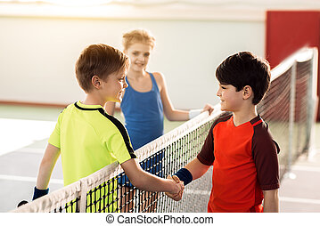 Happy children ending sport competition by handshake