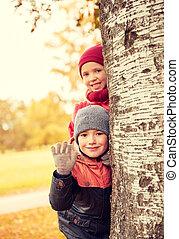 happy children hiding behind tree and waving hand -...