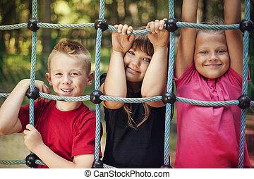 Happy children holding a net on playground