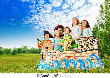 Happy children in costumes standing on ship