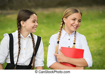 Happy children in pigtails smile in formal uniforms after school day outdoors, happiness.
