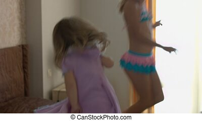 Happy children jumping on the bed and having fun