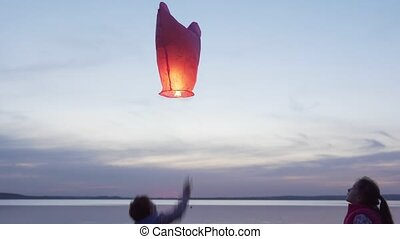 Happy children launch sky lantern by sea at sunset - Happy...
