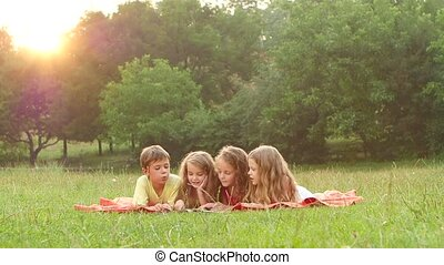 Happy children leaf through a book in the garden on the lawn...