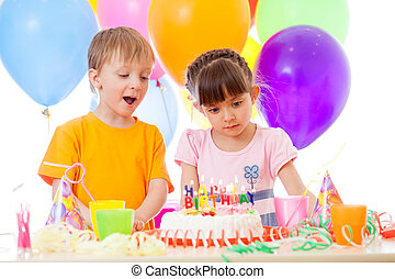 Happy children look at birthday cake