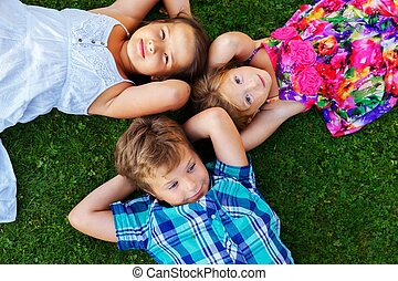 Happy children lying on a meadow