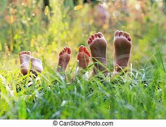 Happy children lying on green grass