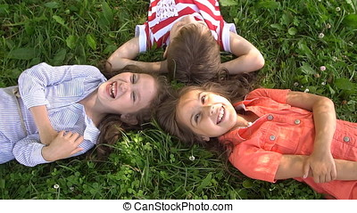 Happy children lying on the grass laughing together, Slow Motion