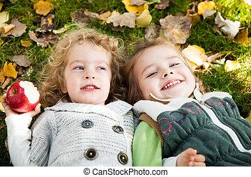 Happy children lying outdoors