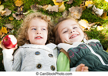 Happy children lying outdoors