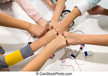 happy children making fist bump at robotics school -...
