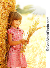 happy children on a field with bales harvest in autumn
