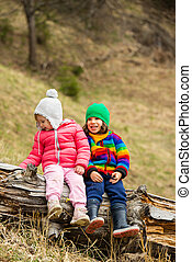 Happy children on tree trunk