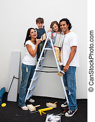 Happy children painting a room with their parents