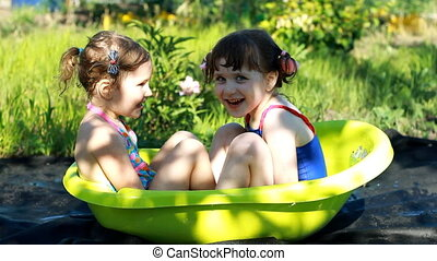 Happy children playing and bathing in the water in a sunny summer day outdoors