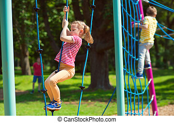Happy children playing at playground in summer