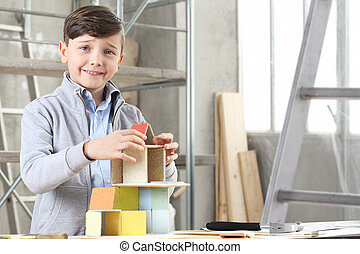 Happy children playing building a house with construction models at interior site. House buy and building goal concept