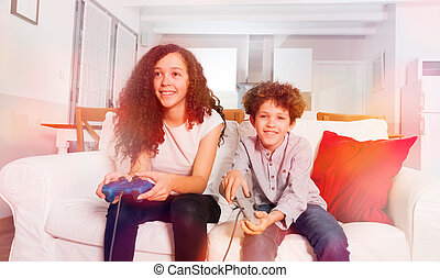 Happy children playing computer games at home