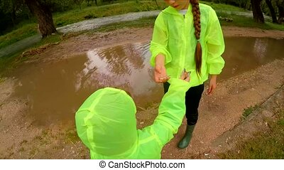 Happy Children Playing In Puddles In Park