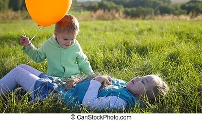 Happy children playing in the Park. Balloon. The laughter and smiles of children