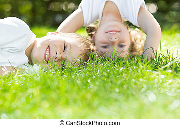 Happy children playing on green grass in spring park....
